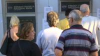 People wait at a bank's cash machines in Greece