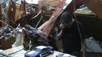 Householder standing amongst tornado debris