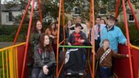 Children around a new wheelchair swing