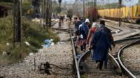 Migrants walk towards the railway station in the Macedonian town of Gevgelija