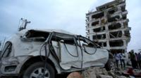 Somali government soldiers and journalists stand near a car destroyed in front of the Jazeera hotel after an attack in Somalia's capital Mogadishu