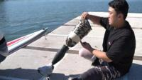 Ha Jae-heon fits his prosthetic legs next to his boat