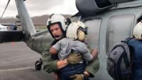 US Navy officer carries young boy off a helicopter
