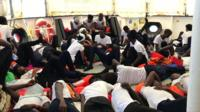 Dozens of migrants in identical white t-shirts and dark trousers lie on the deck of the Aquarius