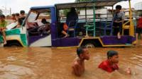 Children play at an area flooded after heavy rains in Jakarta