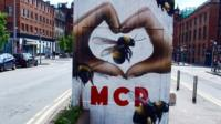 Graffiti showing hands in a heart shape around a bee, and MCR initials