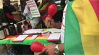 Man wearing Zimbabwean flag holding maracas