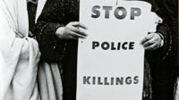 A woman holding a sign 'Police Stop Killing' taken from the book 'The Fire Next Time' by James Baldwin