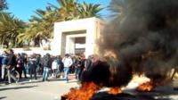 Young Tunisian graduates block the road with burning tyres in Sidi Bouzid in solidarity with protest in the central Tunisian town of Kasserine