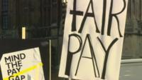 Protest placards reading 'Mind the Pay Gap' and 'Fair pay'