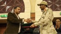 Ahmad al-Rabiah and Mohamed Hamdan Dagalo shake hands