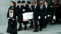 K-pop singers carry the coffin of Jonghyun while his sister walks in front, carrying his photo