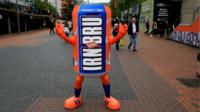 Performer wearing a giant Irn-Bru can mascot outfit