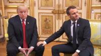 Emmanuel Macron gives US president Donald Trump an awkward leg rub on 10 November 2018