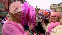 Two ladies dressed in pink holding balloons