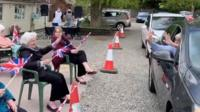 Families wave at care home residents