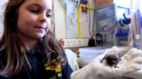 Nine-year-old Ruby holds a bat