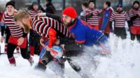 Snow rugby players tackle
