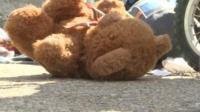 Teddy bear next to buggy wheels