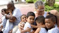 Elderly women hug children from the City of God favela