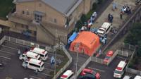 An orange tent and emergency vehicles