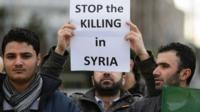 A man holds a placard during a demonstration outside of the United Nations (UN) Offices in Geneva on the opening day of Syrian peace talks