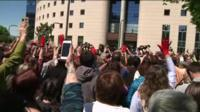 Protesters - some raising a single red-gloved hand - chant in numbers outside the court