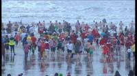 People running into the sea