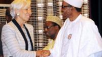 hristine Lagarde (L) shakes hands with Nigeria's President Muhammadu Buhar