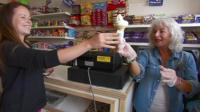 A volunteer serves a customer in the shop