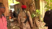 A paramilitary wearing a red beret shouts at some nearby people in this still image