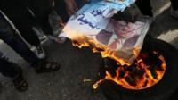 Palestinians burn Trump poster