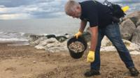 man picking up cigarette butts from a beach