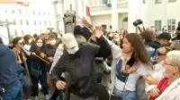 woman trying to pull mask off man