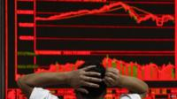 Man with his hands on his head watching falling market figures (in red) on a large screen