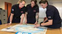 Firefighters looking at map of Antarctica