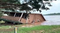 House slides into flooded river