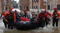 A family is rescued from the centre of York by boat during severe flooding