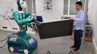 Robot helping a man lift a panel