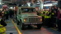 Workers clap and cheer as the last Land Rover Defender leaves the production line in Solihull
