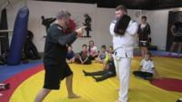 Local martial arts coach Danny Corr demonstrates new techniques to young children
