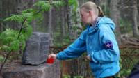 Marina Titova lays a carnation on a grave stone on Mudyug Island