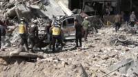 Rescuers helping after a reported air strike in Idlib