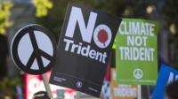 "Protesters hold up placards as they demonstrate against the renewal of Britain""s Trident nuclear weapons system"