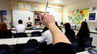 Student with raised hand in class