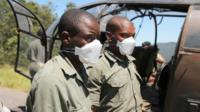 Members of the rescue team wear masks as they prepare to offload a body retrieved from areas flooded in the aftermath of Cyclone Idai in Chimanimani, Zimbabwe, March 21, 2019.