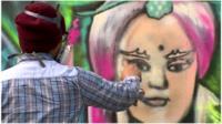 Artist sprays graffiti on a wall