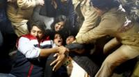 Police detain demonstrators during a protest against the release of a juvenile rape convict