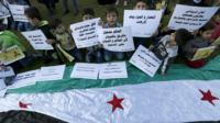 Children carry placards as they call for the lifting of the siege off Madaya and Zabadani in Syria