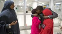Ismail Issack, father of Miski Shalle, 11, and Muzamil Shalle, 14, embraces his children at JFK airport